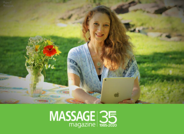 Gael Wood seated outdoors with an iPad and the Massage Magazine logo